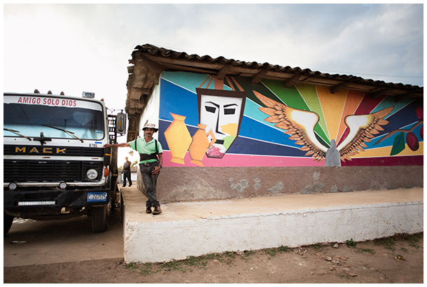 Male worker standing by a graffiti wall in Honduras